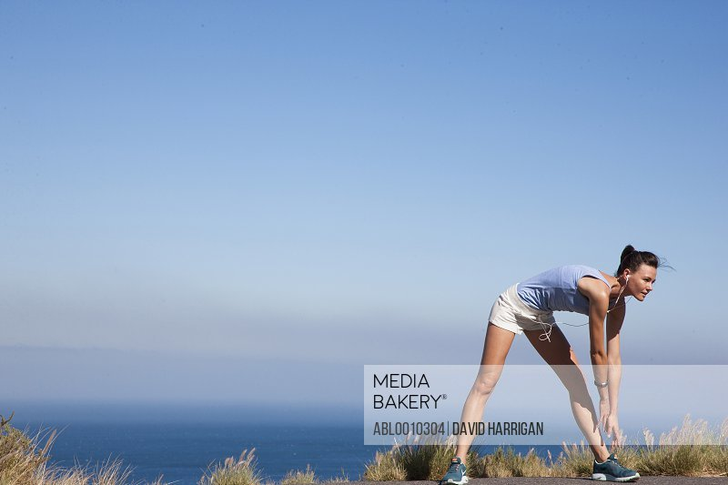 Woman Stretching against Ocean and Blue Sky