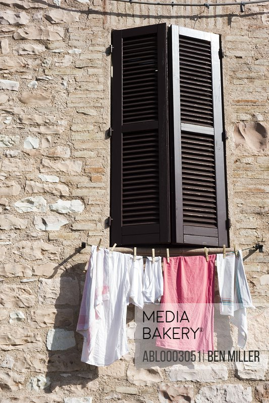 Clothes Hanging under Window with Shutters