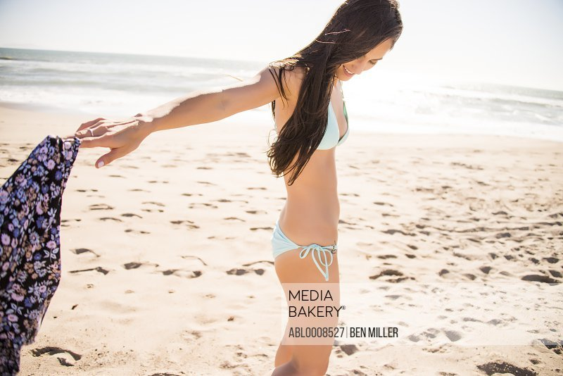 Woman on Beach with Arms Outstretched Holding Shorts