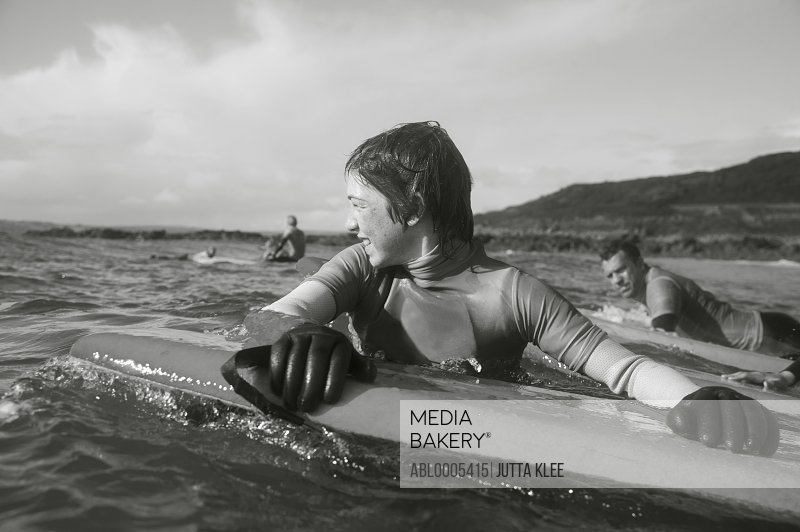 Teenaged boy in the sea holding on to his surfboard
