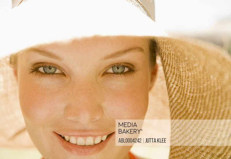Close up of young beautiful woman with hat smiling