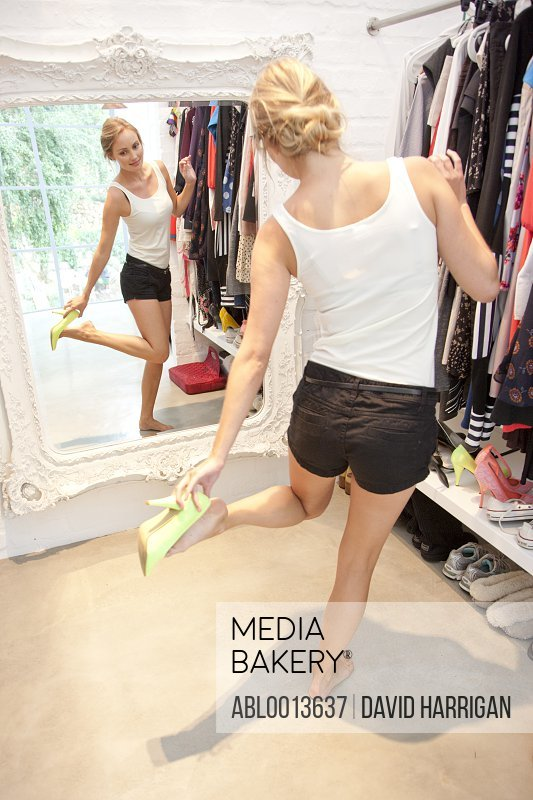 Woman in Closet Looking in Mirror Trying on Shoes