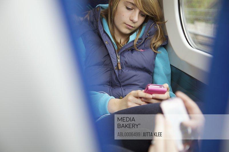 Teenage Girls Sitting on Train Using Smartphones