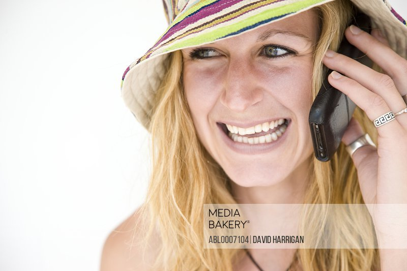 Woman Wearing Striped Hat Using Cell Phone
