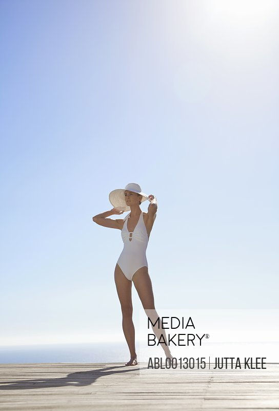 Woman in white hat and swimsuit standing on a sun deck holding the brim of her hat