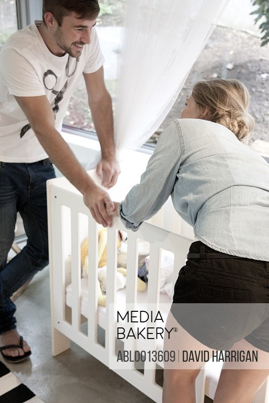 Young Couple Standing over Baby Crib