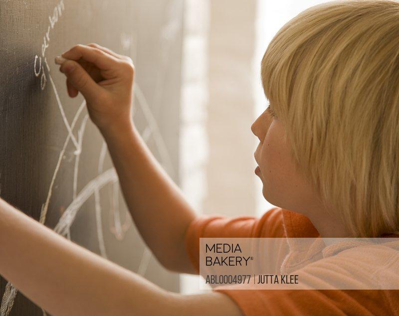 Young boy writing on a blackboard