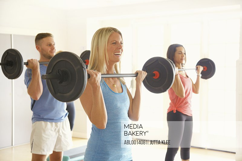 Three People Lifting Barbells at Fitness Class