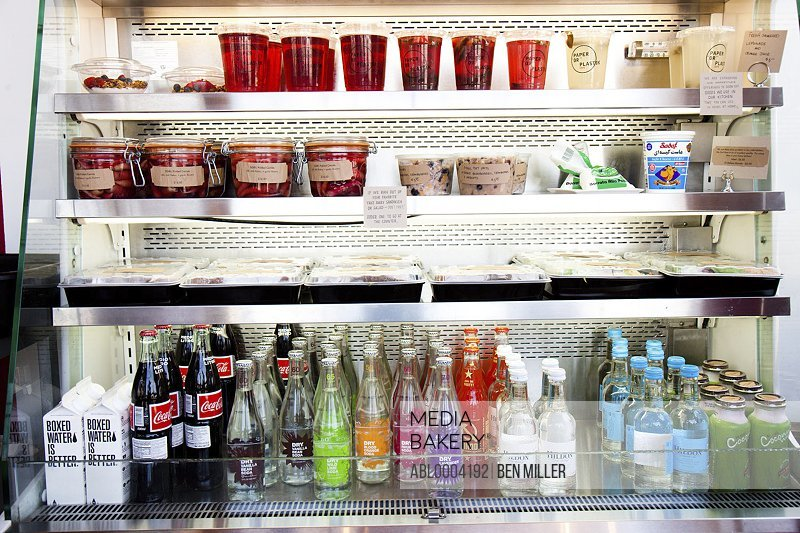 Shop Refrigerator Shelves Stacked with Food Containers and Soft Drink Bottles
