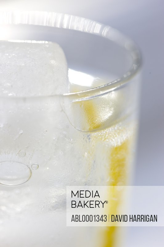 Close up of a glass of water with ice and sliced lemon