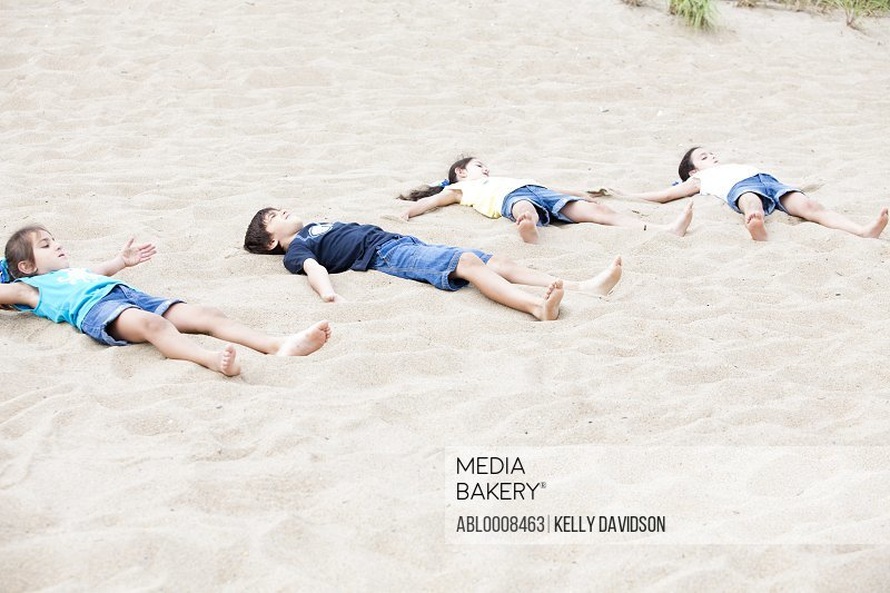 Children Lying on Sand on Beach