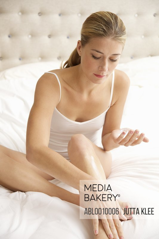 Woman Sitting on Bed Applying Body Lotion on her Leg