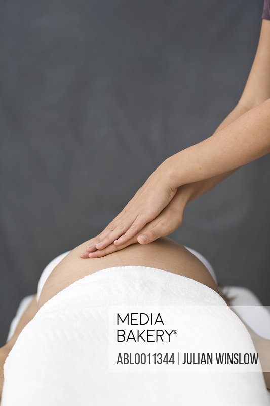 Close up of massage therapist's hands massaging pregnant woman stomach