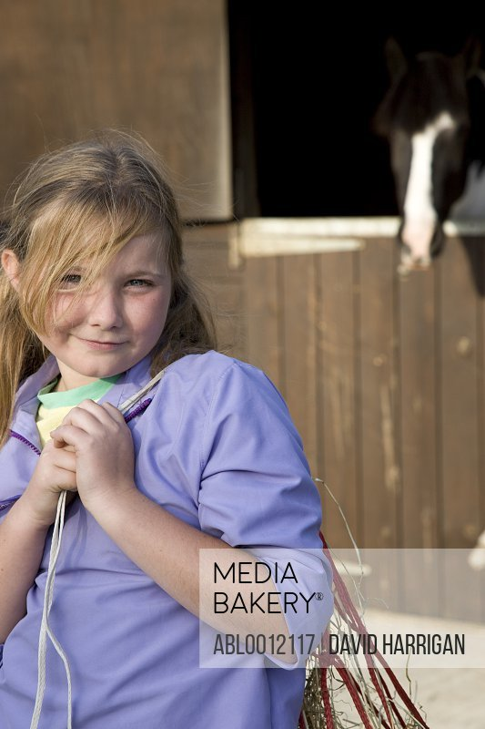 Young girl standing in front of stable carrying a net bag over her shoulder