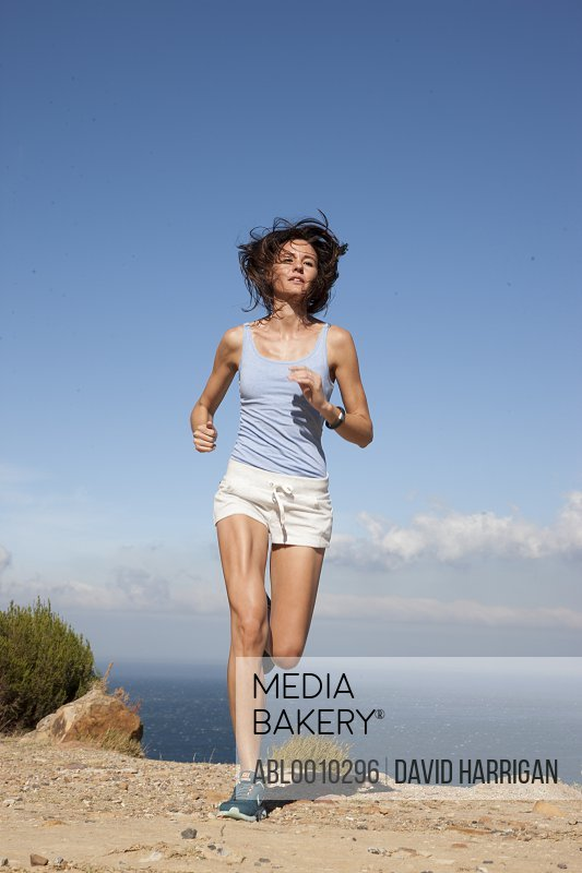 Woman Running along Cliff by Ocean