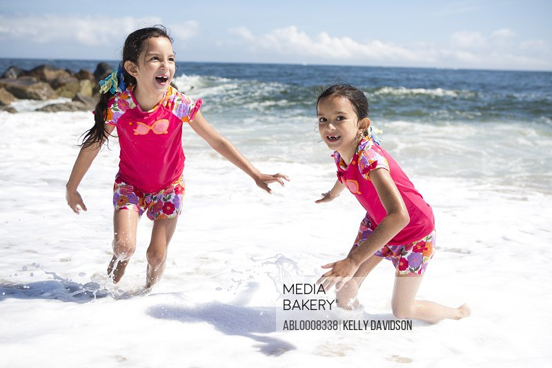 Twin Girls in Matching Outfits Playing on Beach