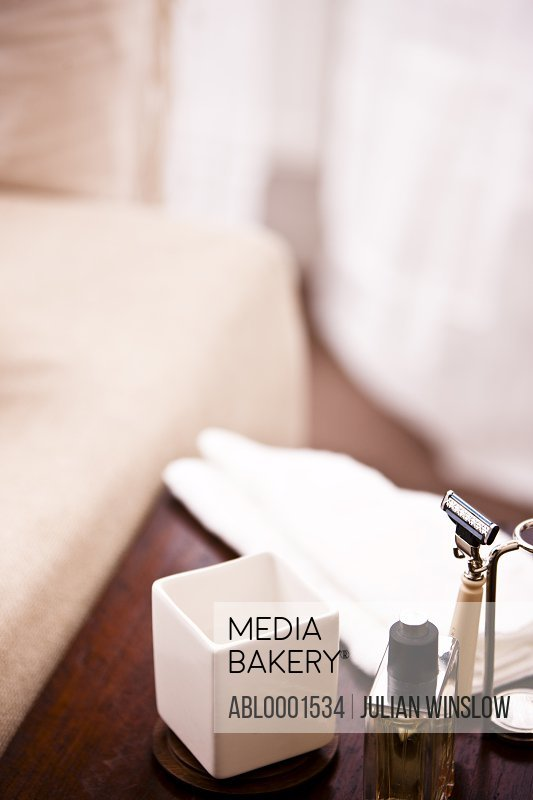 Close up of shaving equipment and a perfume bottle on a wooden table