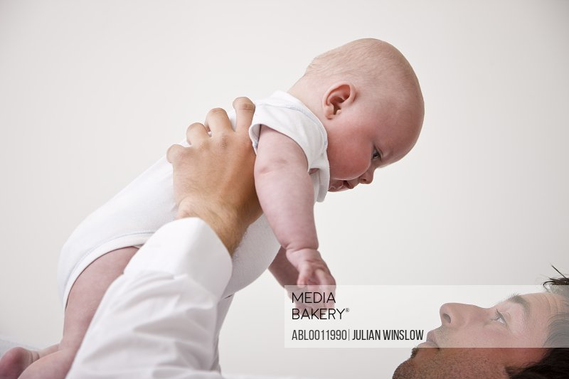 Man lifting baby over his head