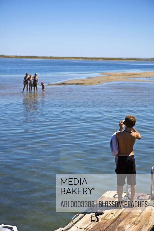 Boy Taking Photo of Family from Jetty at Seaside