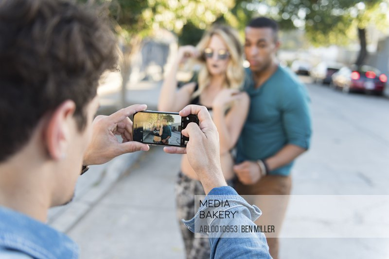 Back View of Man Taking Photo of Friends