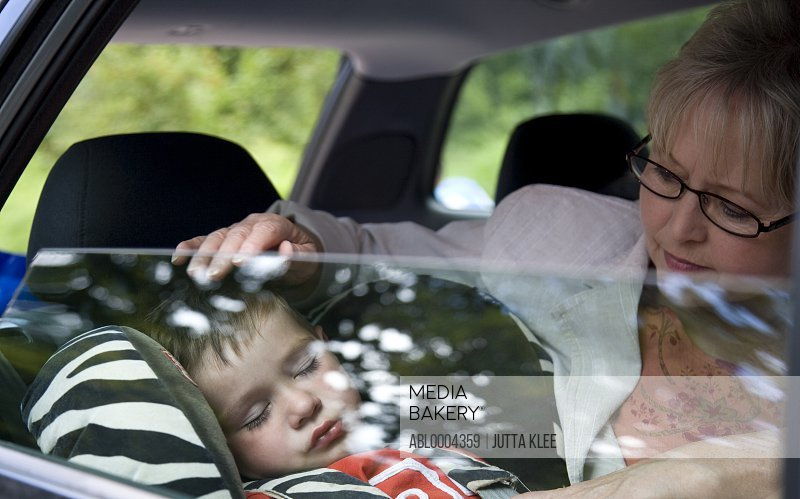 Grandmother looking after sleeping grandson