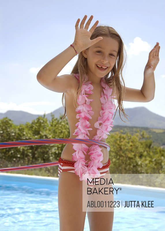 Girl with hula hoop and pink garland around neck by swimming pool