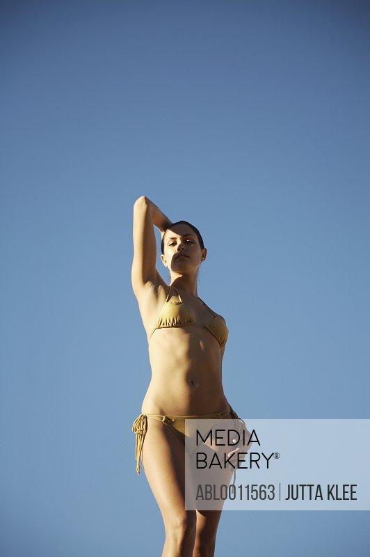 Portrait of a woman standing against blue sky
