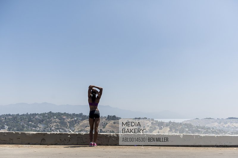 Sportswoman Stretching Looking at View