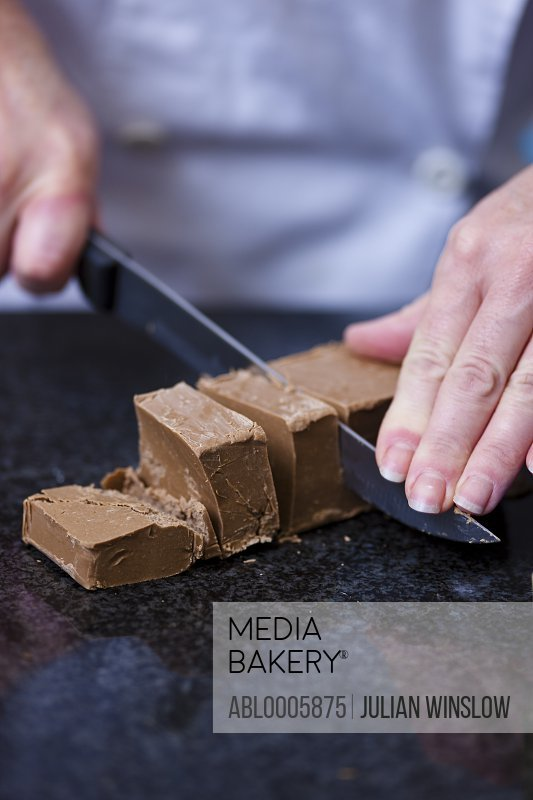 Close up of a chef's hands cutting a chocolate block