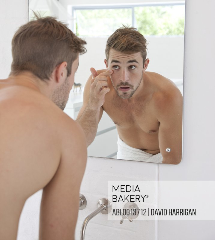 Man in Bathroom Looking in Mirror Checking his Face