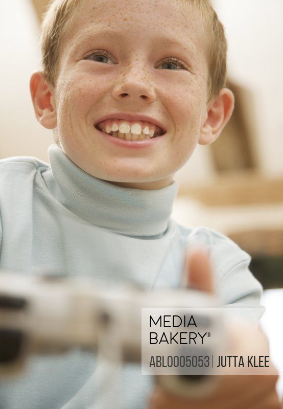 Close up of boy playing and holding a video game control