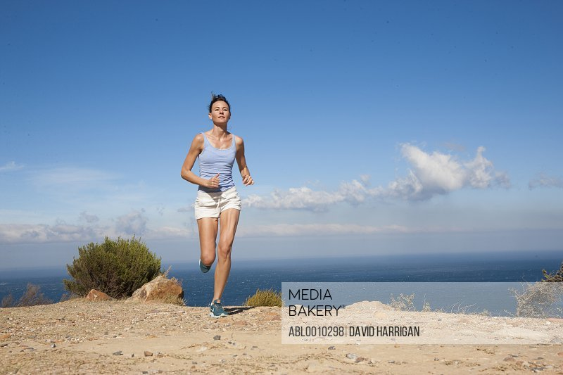 Woman Running along Cliff by Ocean
