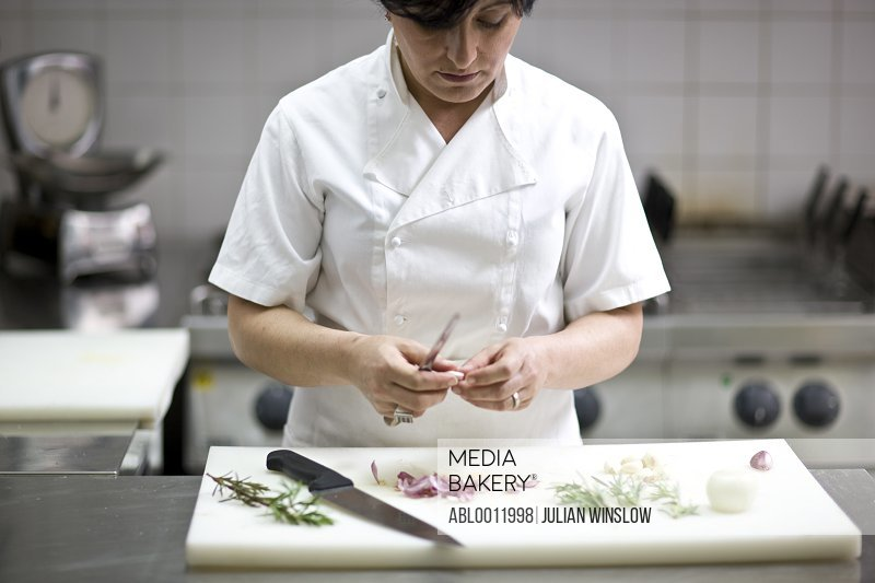 Woman chef peeling garlic with a knife