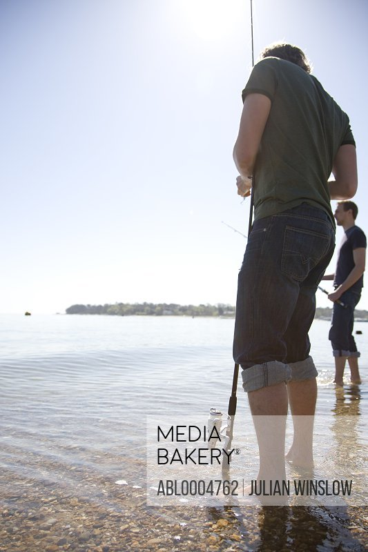 Two men standing in the shoreline fishing