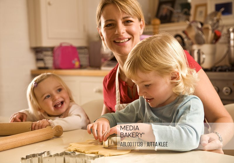 Portrait of young blonde woman with little girls smiling and baking