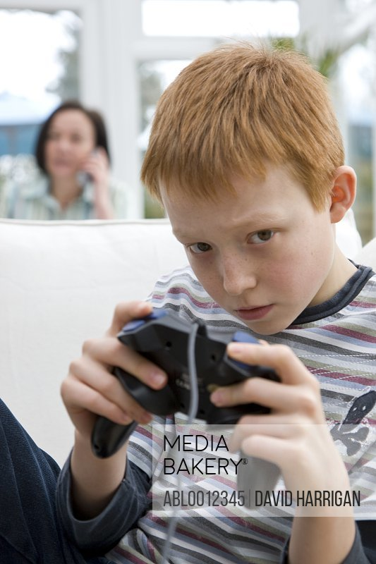 Boy holding a game controller with woman behind him