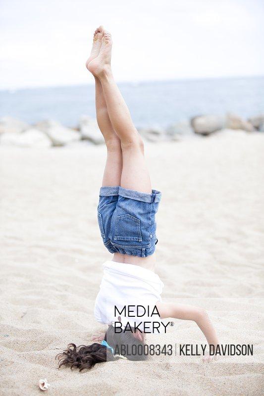 Girl Doing Headstand on Beach