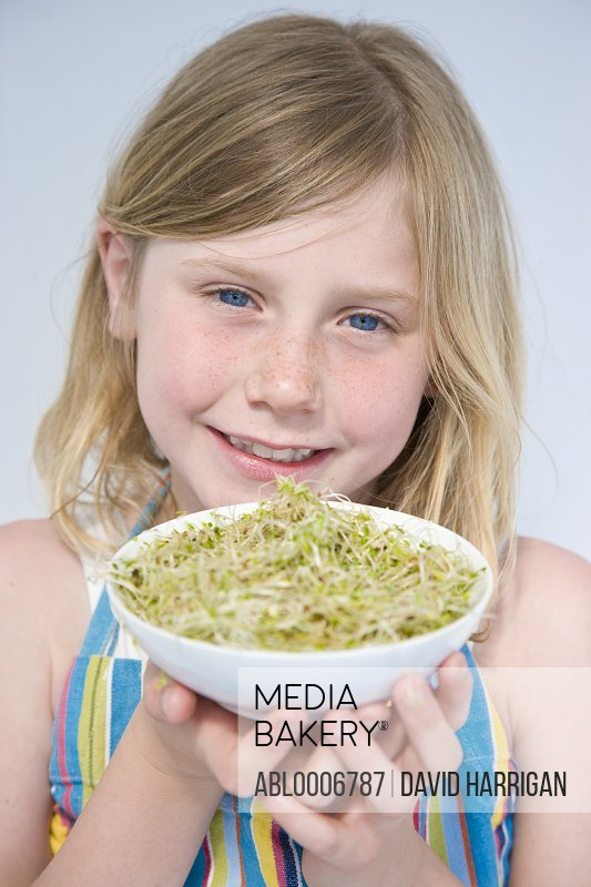 Smiling Girl Holding Bowl of Alfalfa Sprouts