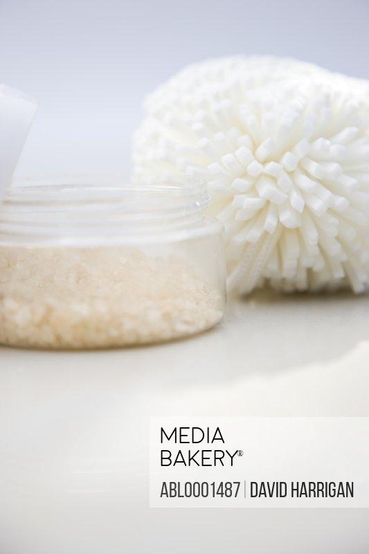 Close up of a jar of bath salts and sponge