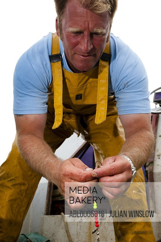 Fisherman attaching a bait to a fishing hook - low angle