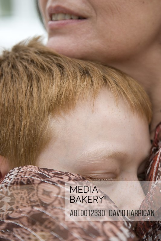 Extreme close up of a woman hugging a sleeping boy