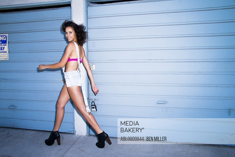 Young Woman Walking beside Garage Doors Smiling