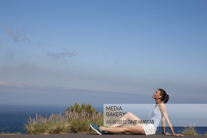Sport Woman Sitting on Road against Ocean and Blue Sky