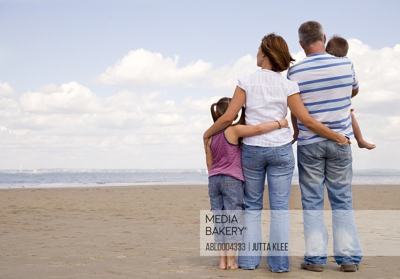 Back view of young family on a beach