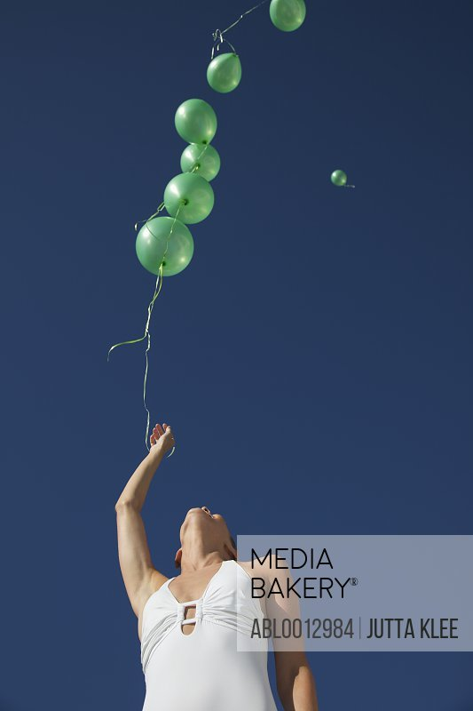 Woman releasing green balloons in a cloudless sky - low angle view