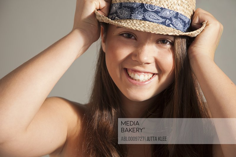 Close up of Teenage Girl Pulling down Straw Hat on Head