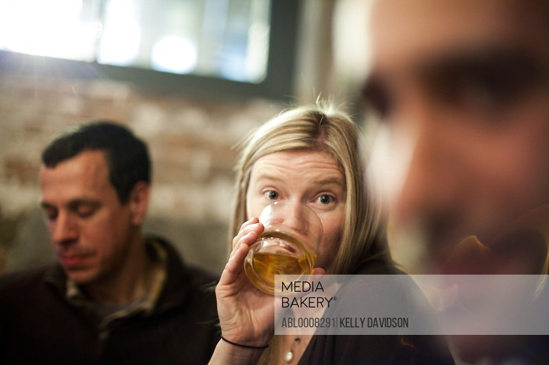 Woman Drinking in Bar with Friends