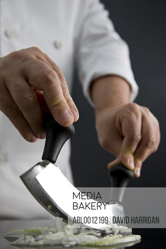 Close up of a chef hands chopping an onion with a double blade mezzaluna knife