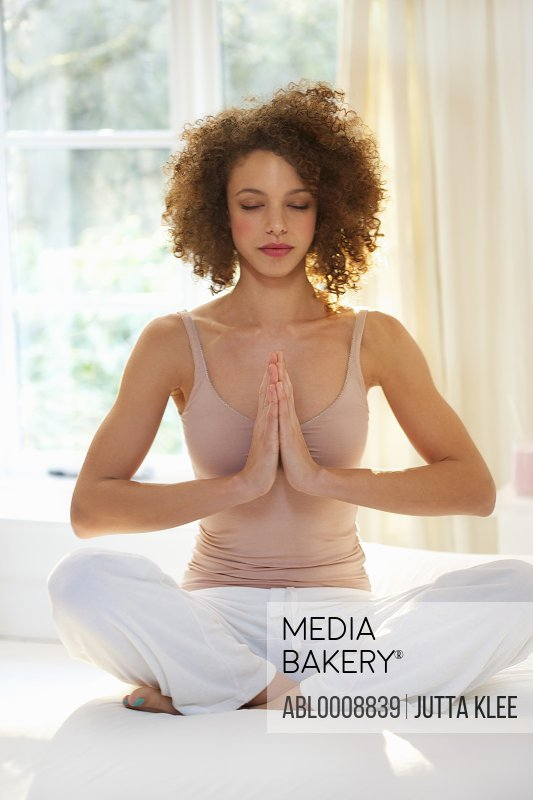 Woman Practicing Yoga with Hands Together