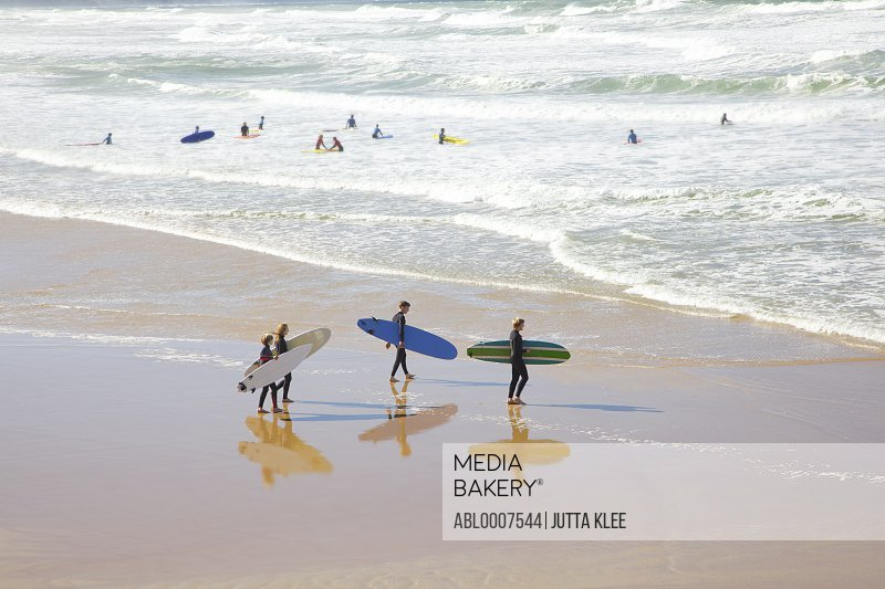 Group of Surfers Walking toward Ocean Carrying Surfboards